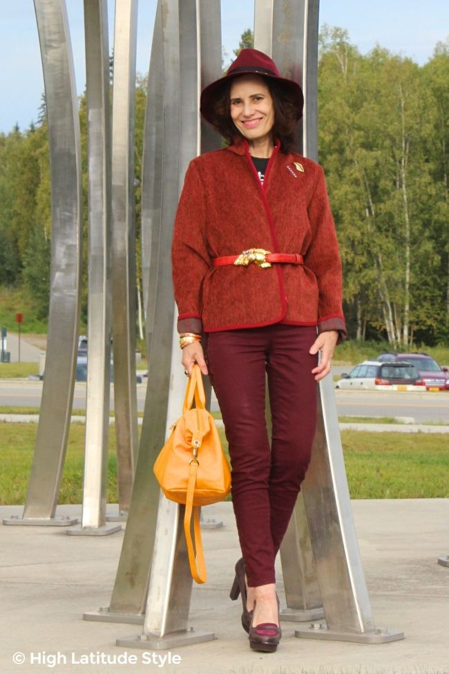 #fashionover50 #tenthstreet woman with fedora, burgundy jeans and jacket plus yellow pilage