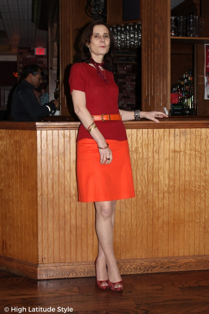 #fashionover50 over 50 blogger Nicole in red top and pumps, orange skirt and belt