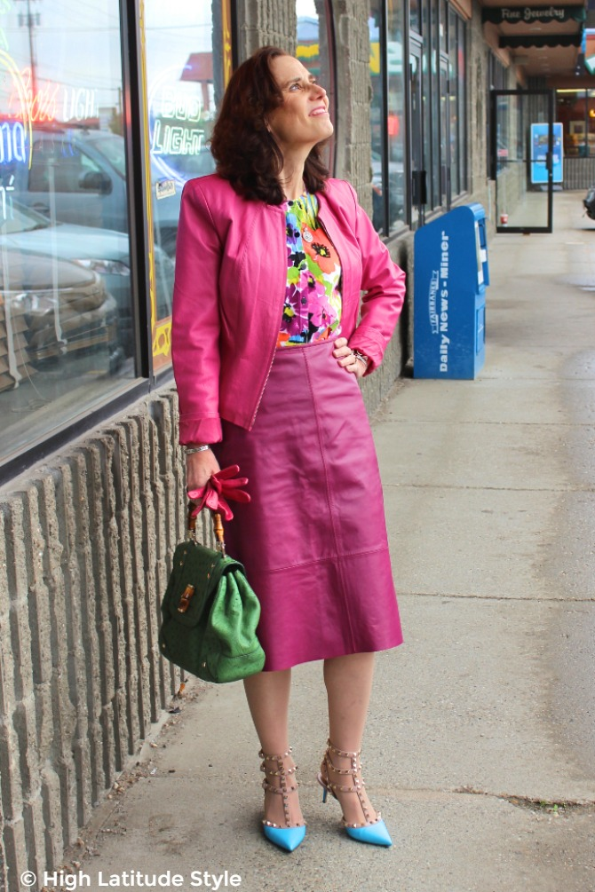 mature woman in pink leather suit with floral top and rock studs