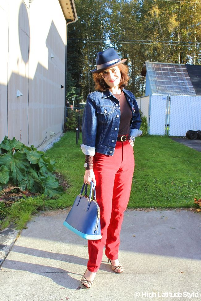 street style blogger in red suede pants, denim jacket, brown T-shirt, and blue brown head gear