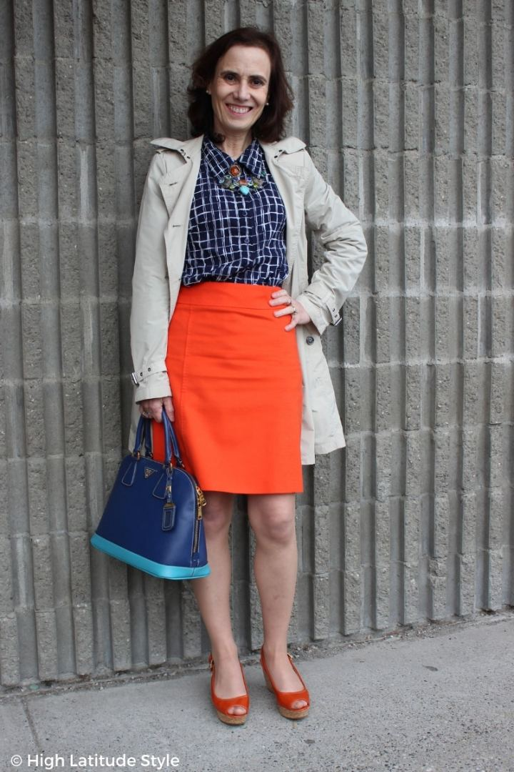 fashion blogger over 50 in fall style work outfit with trench, blue shirt, and orange skirt and sandals