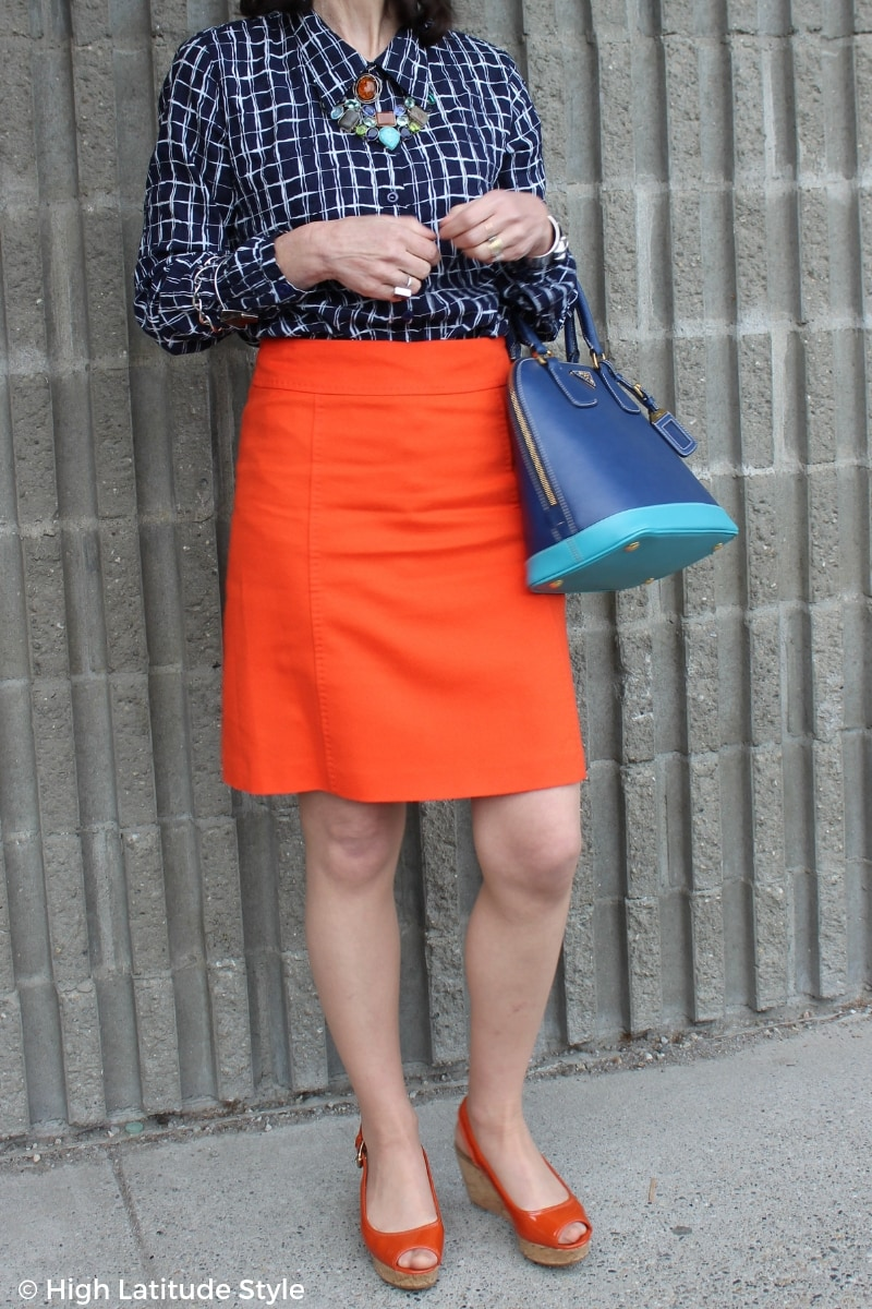 blogger Nicole in an outfit in complimentary colors with blue shirt, bag, orange skirt, sandals and jewelry in both colors