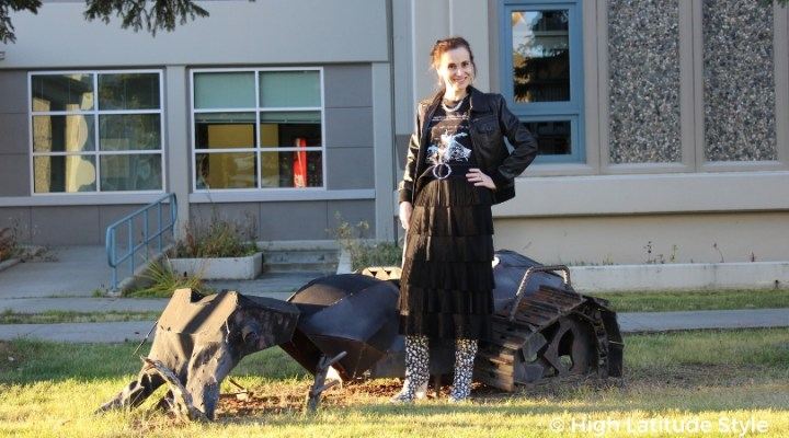 #fashionover40 blogger Nicole in an edgy look with aviator jacket, pleated skirt, graphic Tee and statement boots