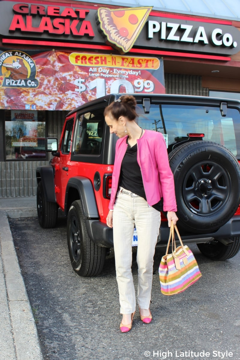 fashion blogger styling a pink leather jacket in fall in front of a red new car