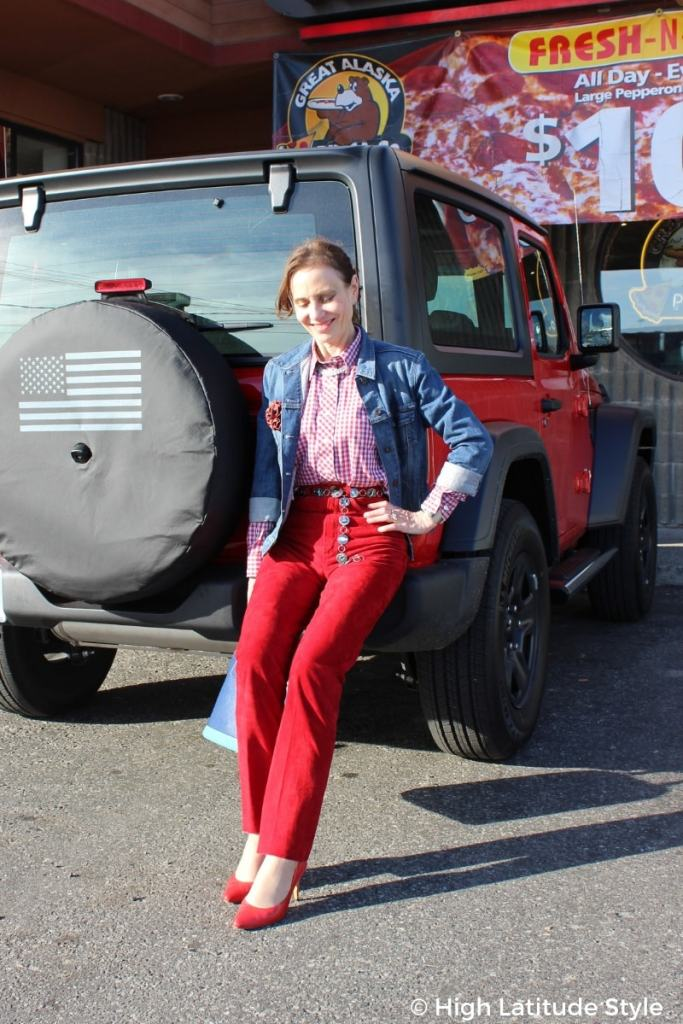 mature fashion blogger Nicole in red trousers, pumps, gingham shirt and denim jacket sitting on a bumper