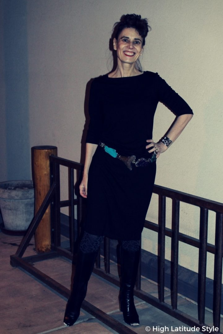 over 50 years old fashion blogger Nicole looking posh and trendy in a LBD, statement belt, and leopard print tights with DIY heel repair
