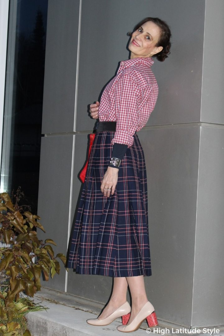 mature fashion book author Nicole Mölders wearing a gingham blouse and plaid wool skirt styled with block heel shoes