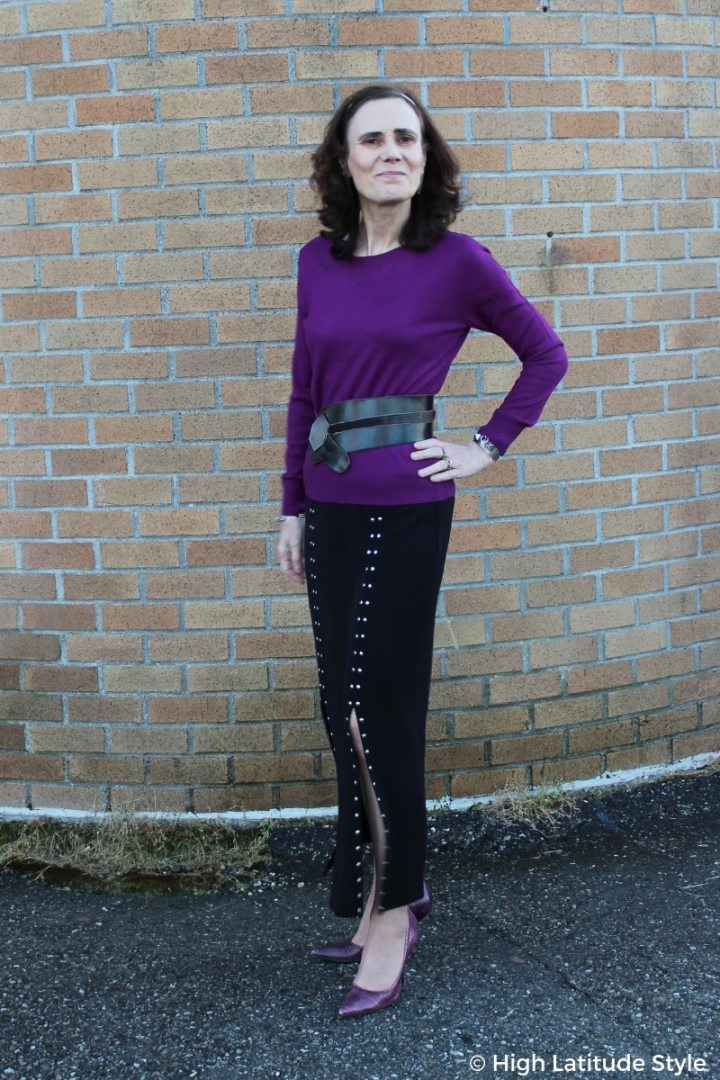 #streetstyle over 50 years old in studded skirt and purple heels and sweater with statement belt
