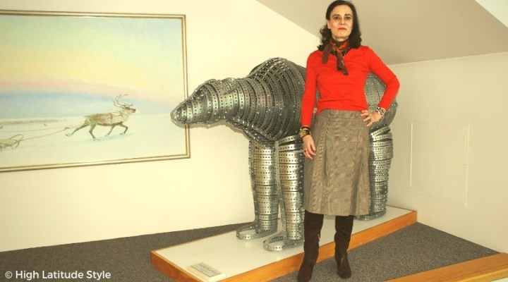 #bloggerstyle Nicole donning a layered T-sheit, v-neck sweater skirt outfit with boots and scarf in front of a steel bear