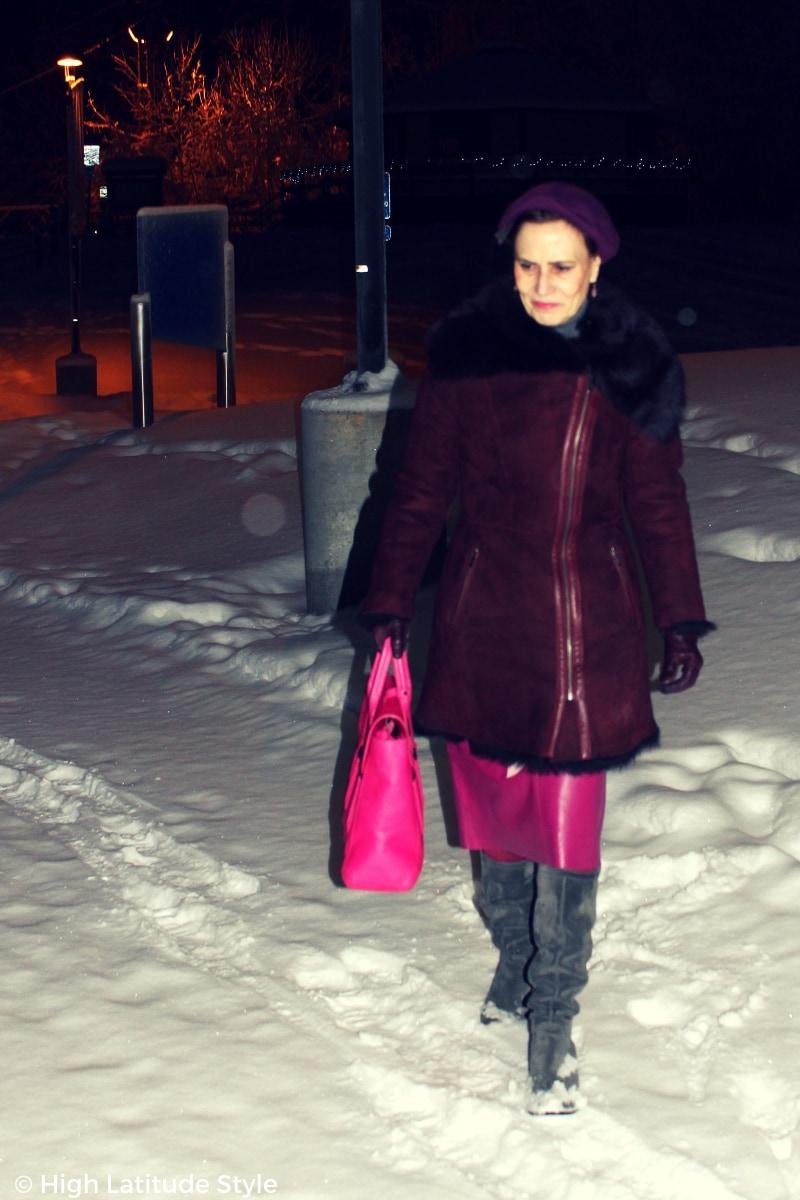 #fashionover50 Alaskan woman walking thru the dark in a shearling coat, booties and beret