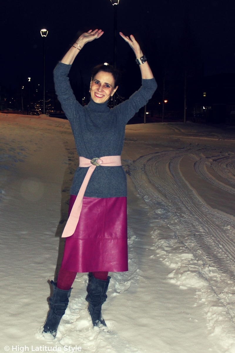 High Latitude Style blogger lifting hands in the dark in the snow wearing a pink gray winter office outfit