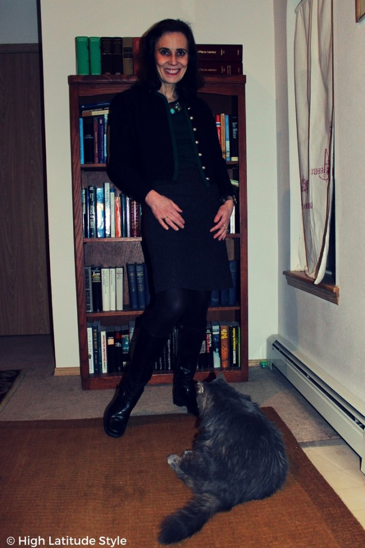 #fashionover50 blogger in casual winter style with gray skirt, black boots, tights, jacket and huntergreen sweater with cat