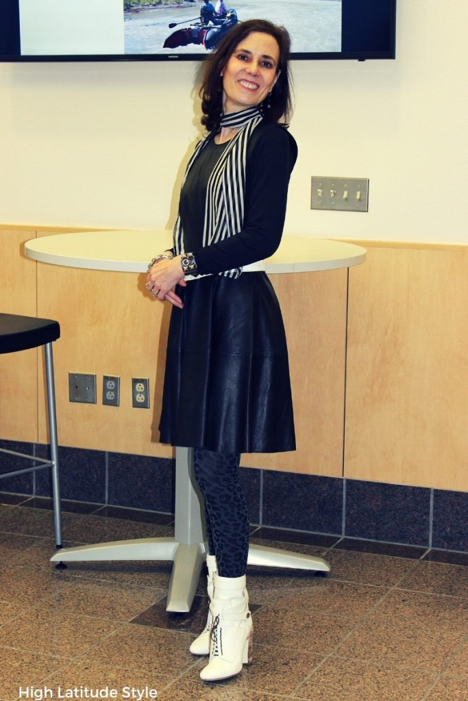 midlife blogger in leather dress with layering piece, black and white scarf, animal print tight and white booties
