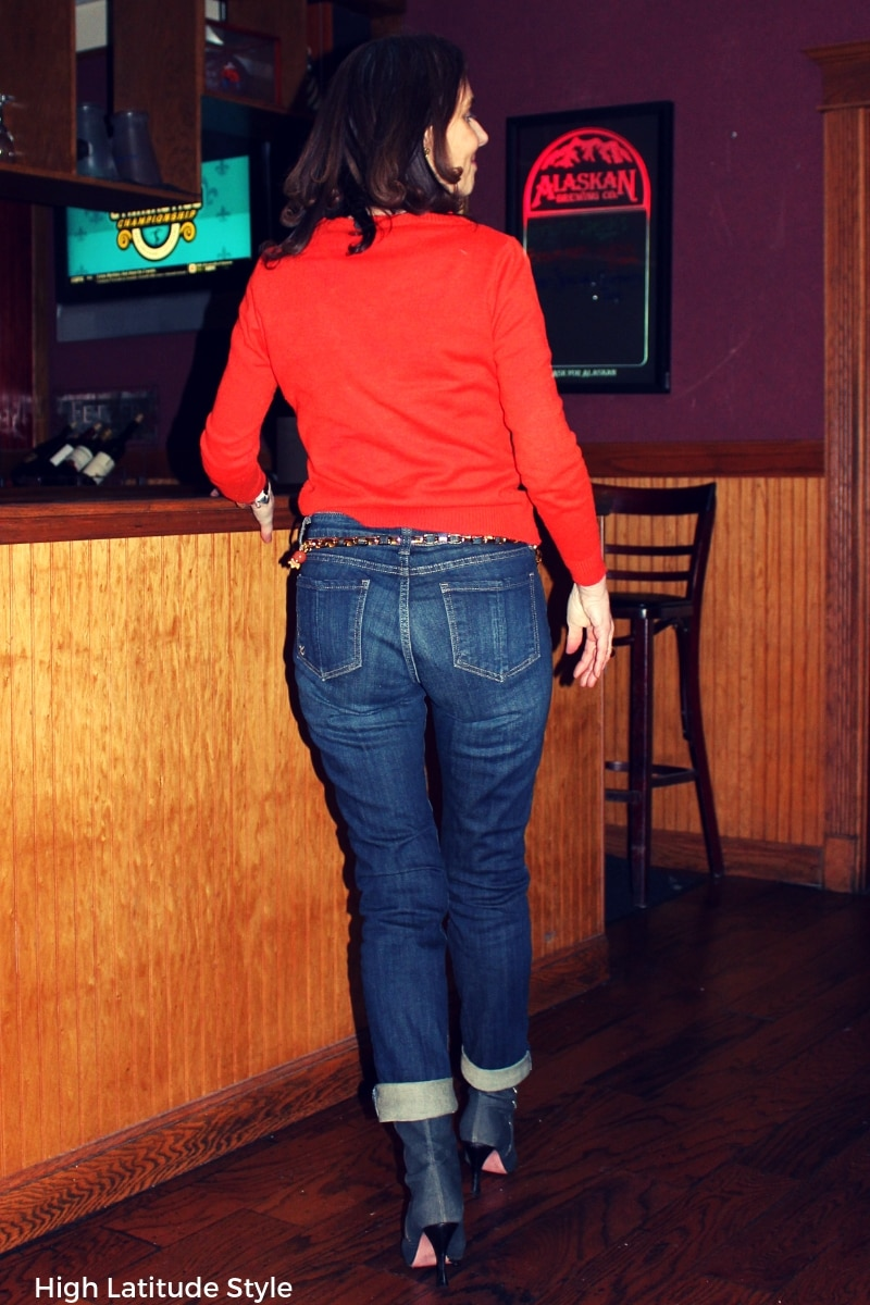 older fashionista reviewing Catherine jean styled with denim footwear, chain belt, orange sweater
