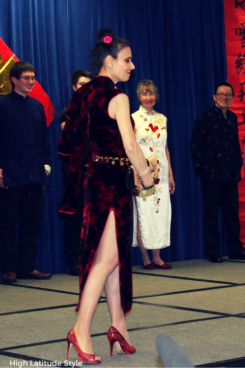 Side view of model in cheongsam with bolero over the shoulder in open-toe pumps