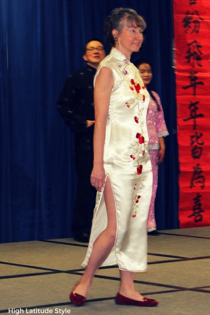 mature woman wearing flat shoes with a white floral embroidered maxi dress