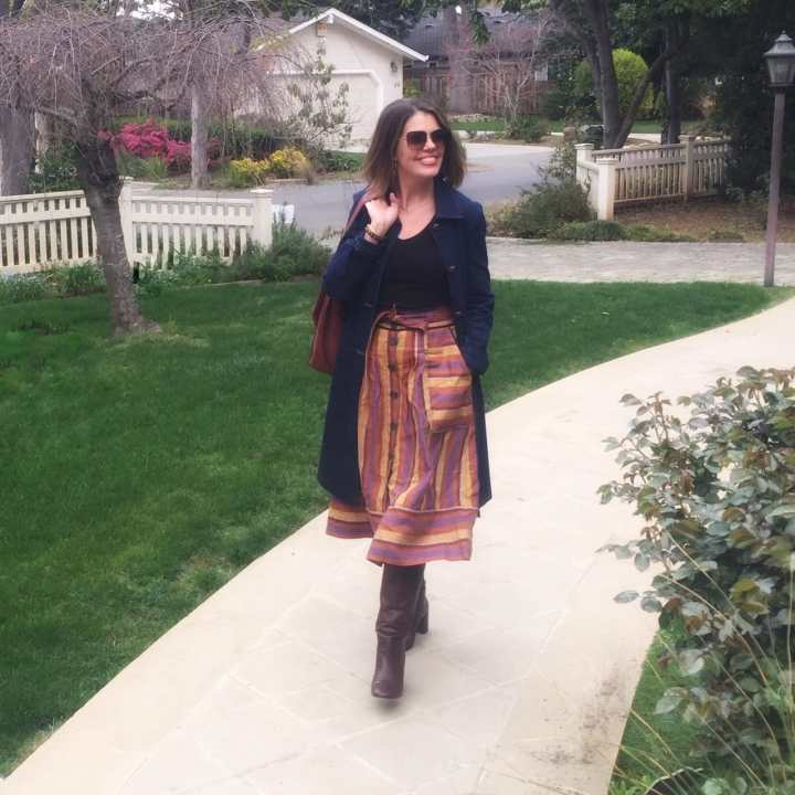 Suzanne Bell looking chic in a line skirt, boots, Tee and trench coat