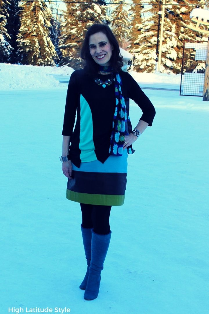 #styleover50 style blogger Nicole in an aqua, green and black comfort tops work outfit with tall boots, assymmetric T-shirt and striped leather skirt