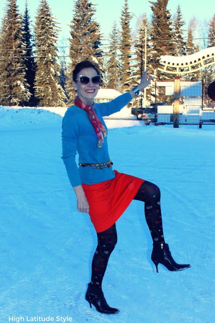 #fashionover50 #streetchic style blogger in floral legwear, orange skirt, turquoise sweater, charm belt and matching scarf