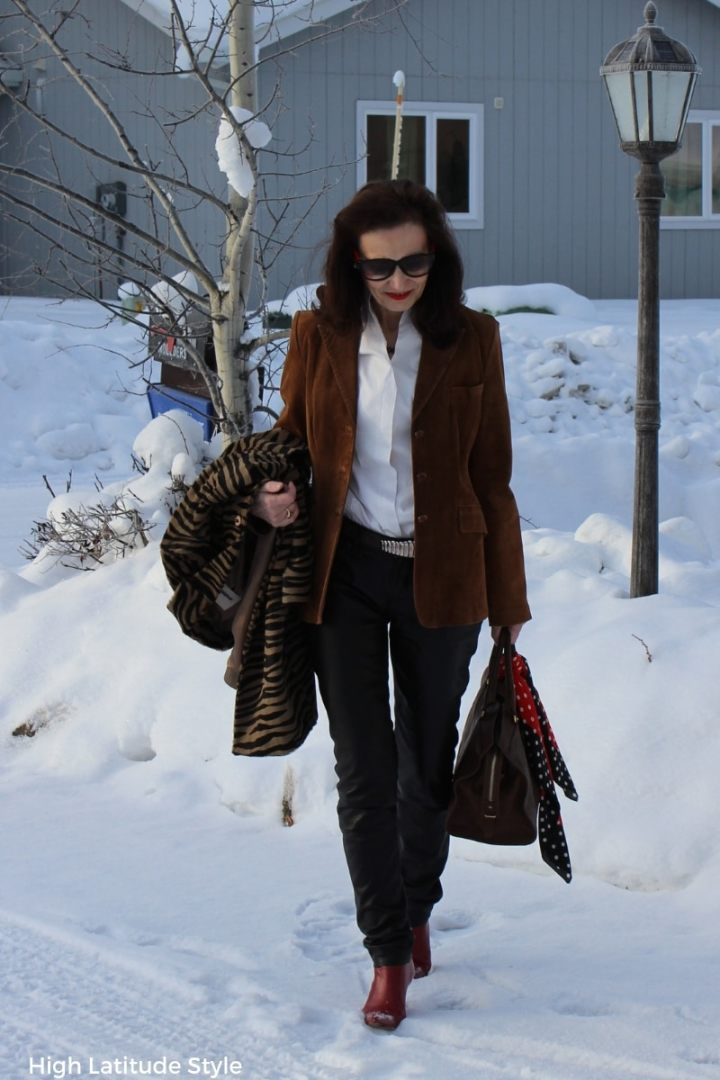 Nicole carrying a coat on her arm while walking thru snow in heels, jacket and pants