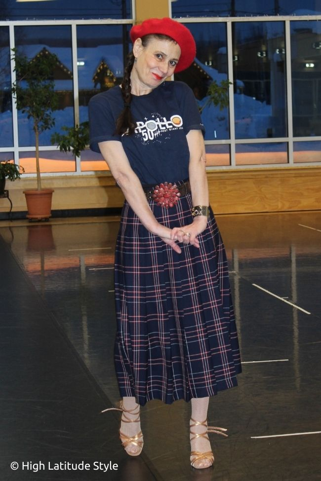 stylist in plaid pleat skirt, graphic Tee, belt sandals