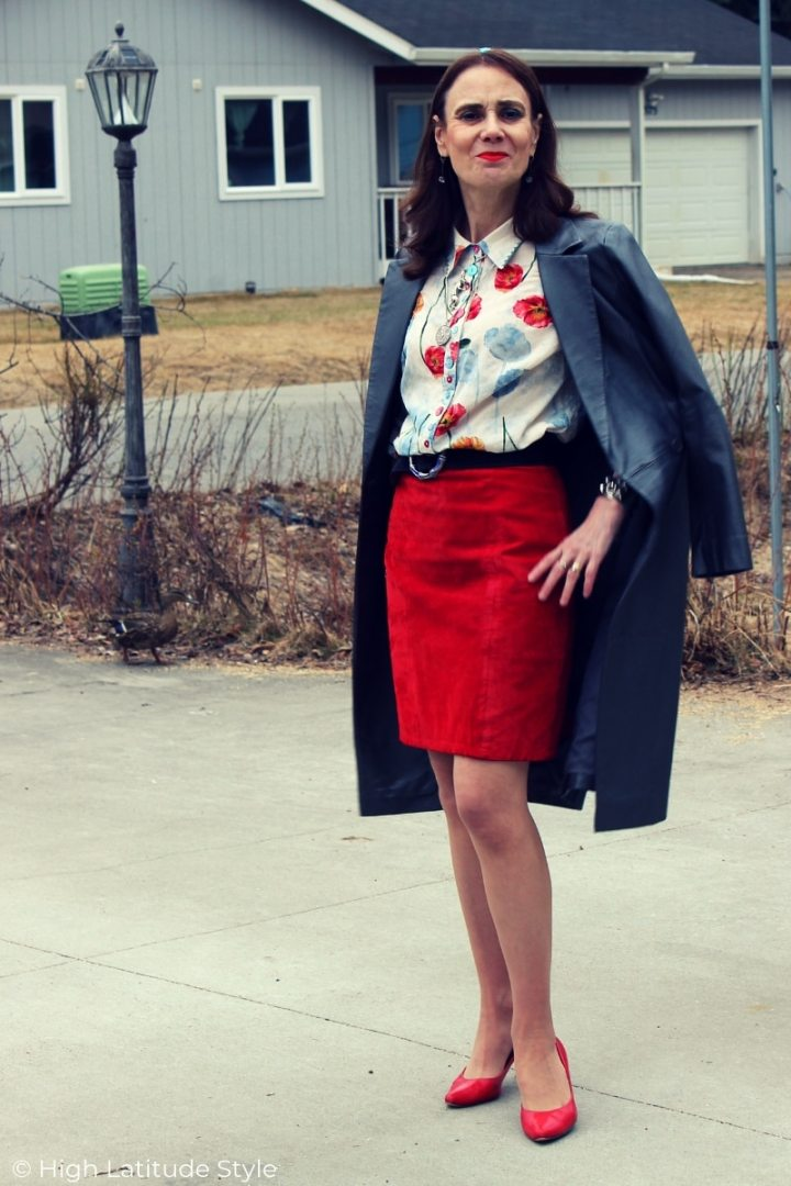midlife woman in spring work outfit with suede skirt, transition season nappa coat and floral blouse