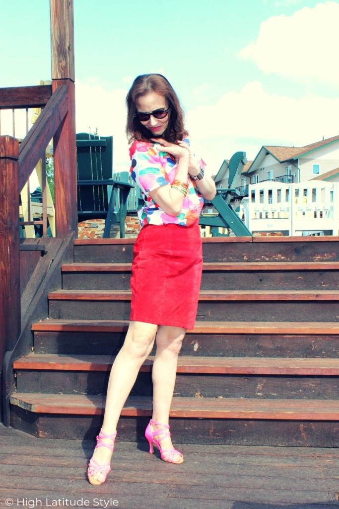 fashion blogger in summer work outfit with abstract print curvy hem top, red skirt, pink strappy sandals and sunglasses