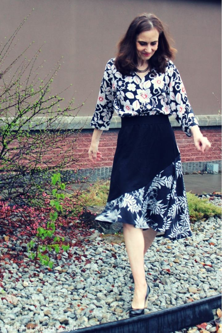 over 50 years old fashion blogger walking in pebble stone in pumps in skirt and shirt