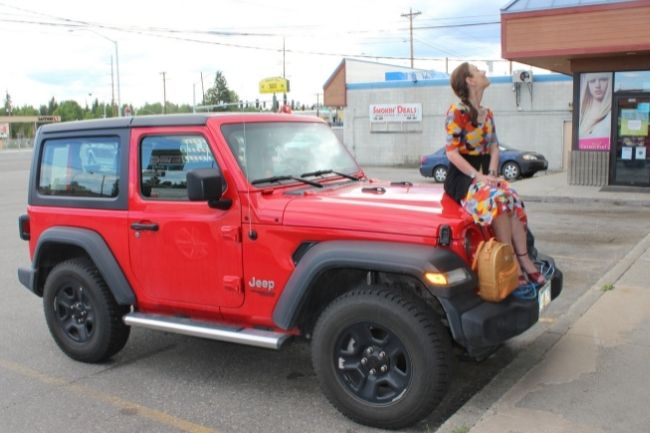 mature woman sitting on a Jeep for a rest in a parking lot in Fairbanks