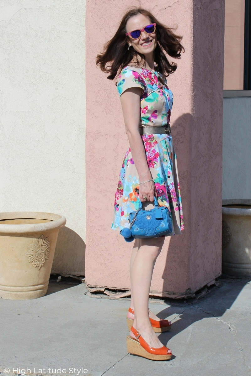 mature blogger in environment-friendly thrifted sandals and cotton summer dress with a bag with pom poms and tags
