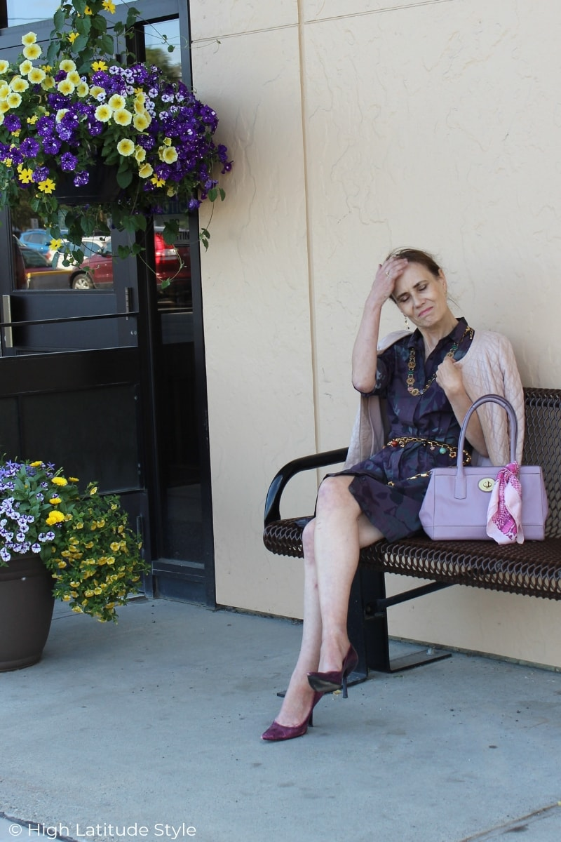 over 50 years old fashion blogger on a bench in shirt dress, pumps, quilted leather jacket