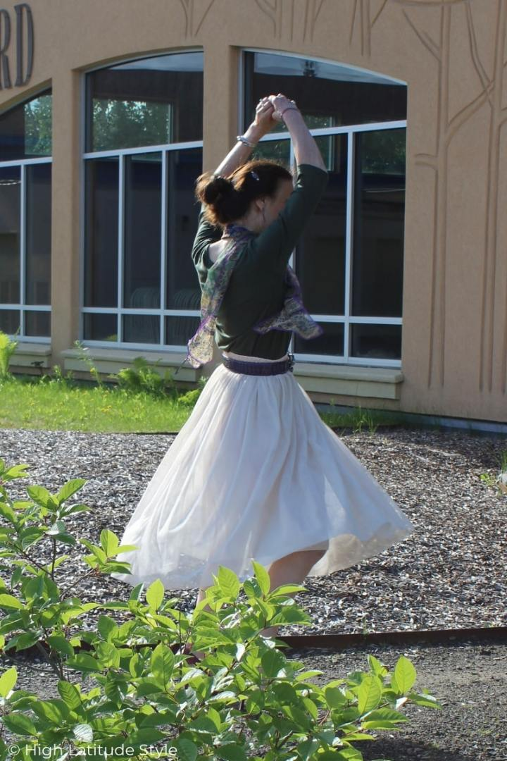 mature woman twirling in a blush and olive dance outfit with scarf