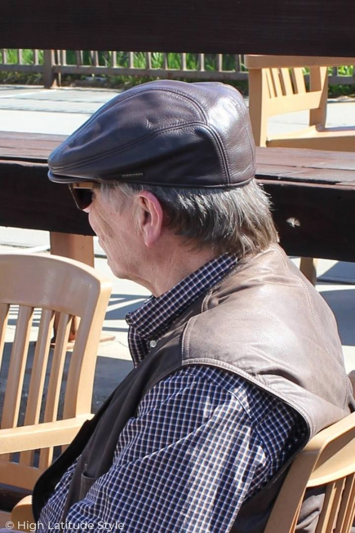 mature man in leather ivy cap and vest over button-down shirt