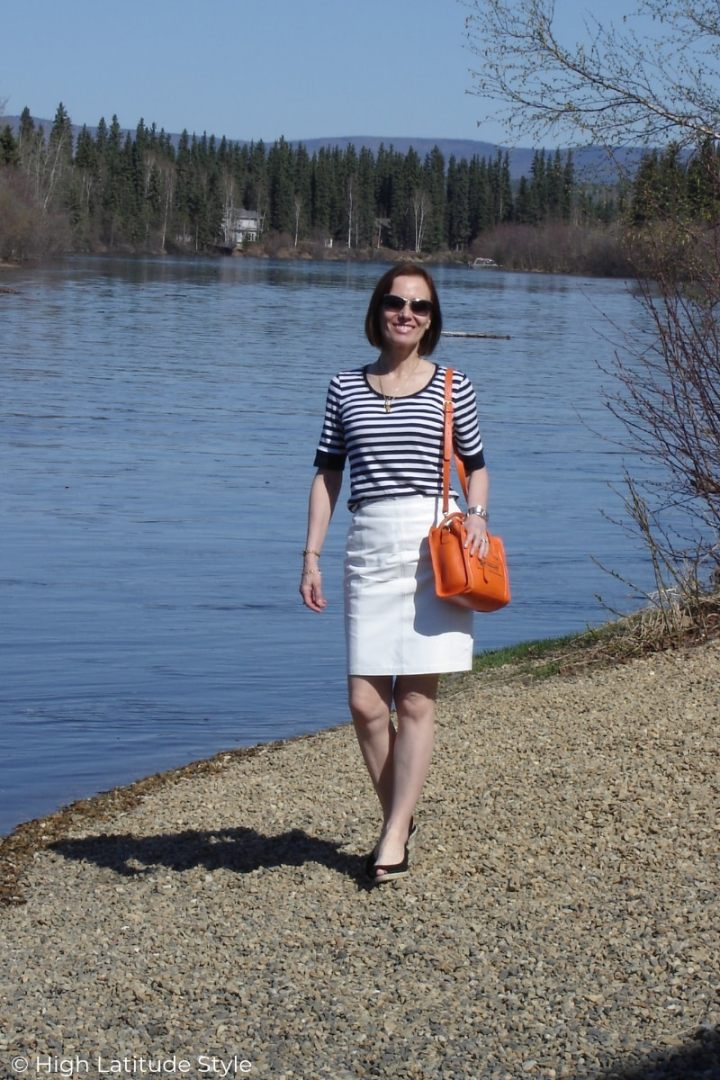 Alaskan style blogger in striped top with leather skirt, esparilles, sunnies and shoulder bag on summer retreat