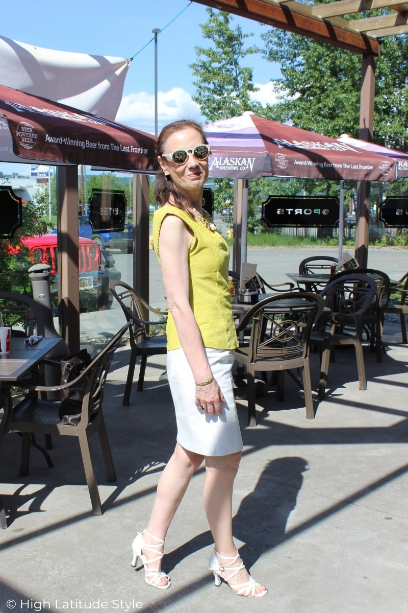 over 50 years old fashion blogger in top and skirt on a sunny day at an outside eating place