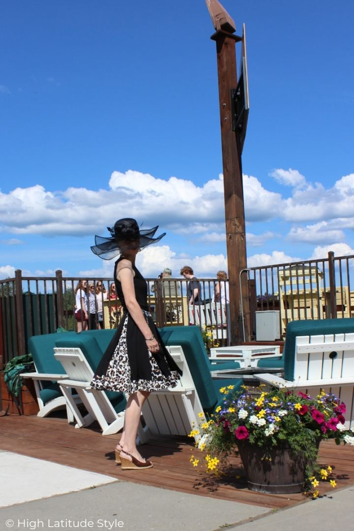 over 50 years old blogger on a deck in a DvF wrap dress with hat