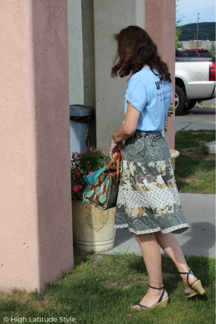 back view of OOTD with college Tee, peasant skirt, wedge sandals, and snake print bag
