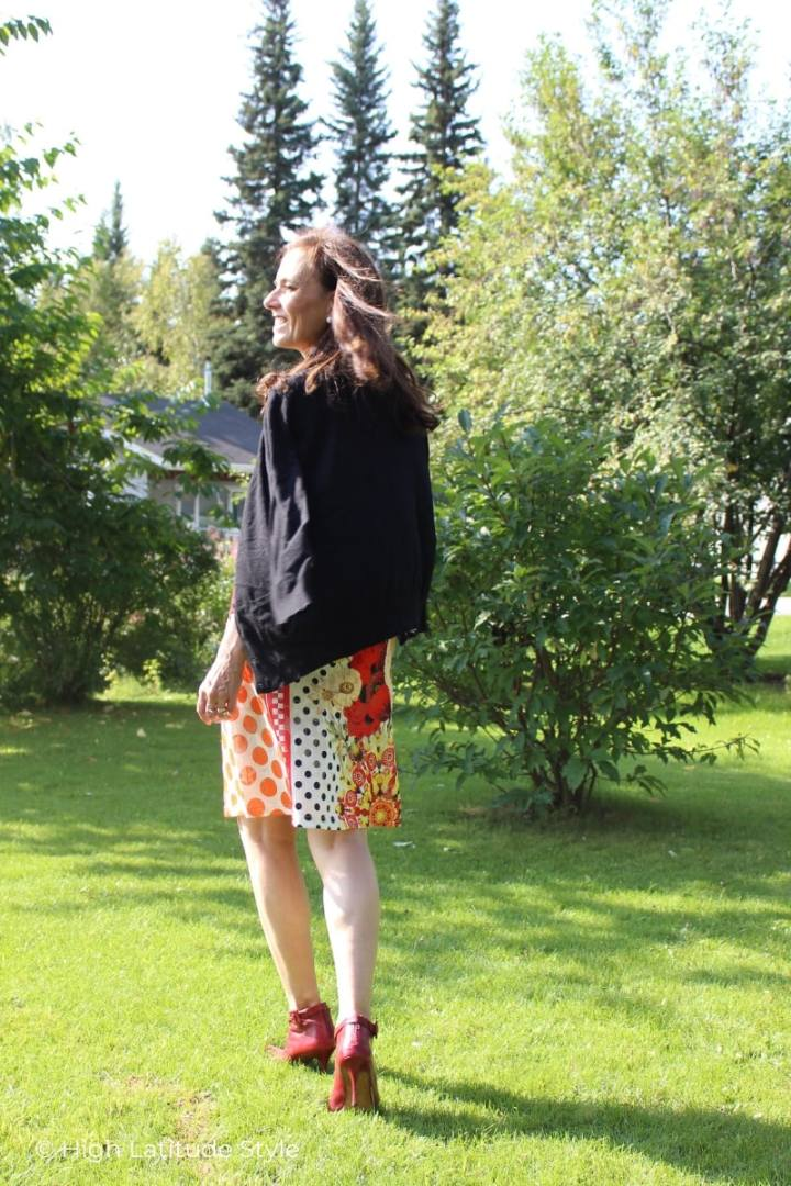 mature woman walking over a lawn in printed skirt, ankle boots and cardigan