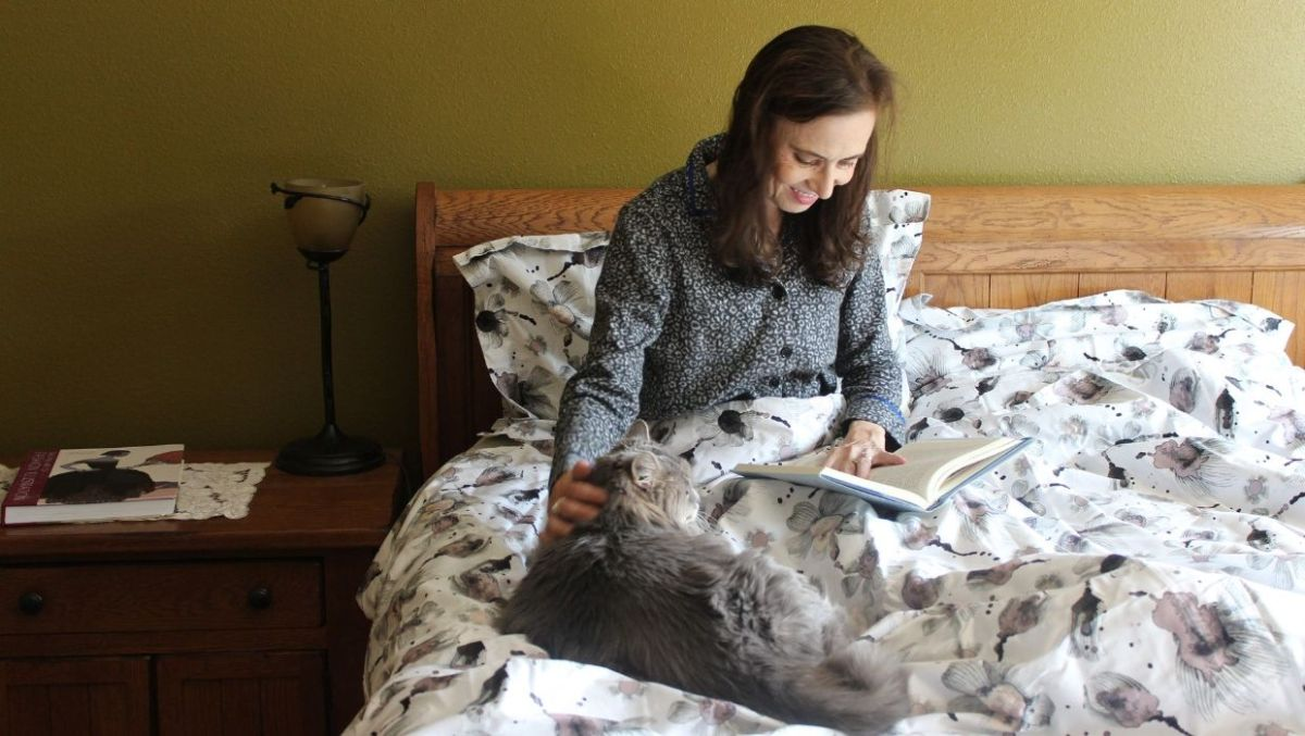 fashion blogger in PJs sitting in bed cotton sateen cover and pillows