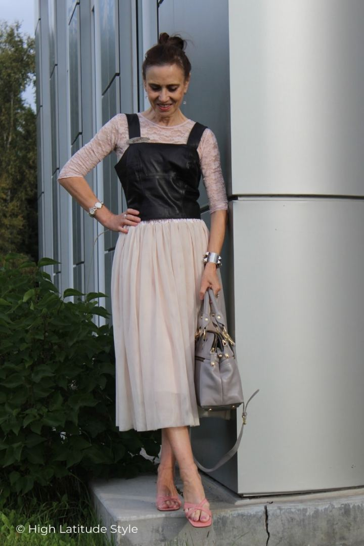 older woman in blush lace top and layered tulle skirt with leather corsage, slides and gray bag