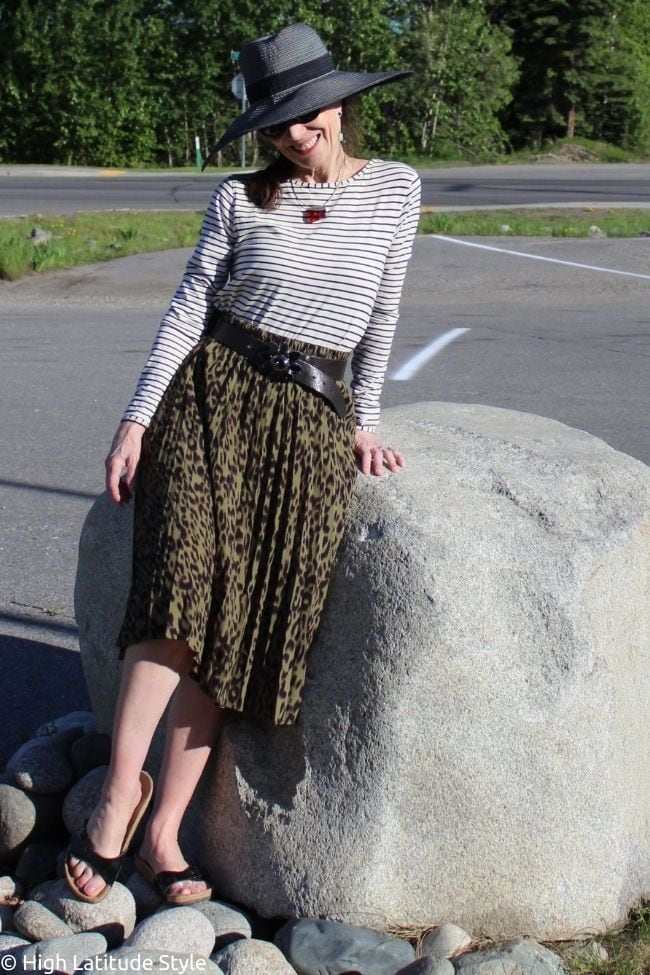 trendsetter in July look with olive printed skirt, long sleeve shirt, statement buckle, hat, slides