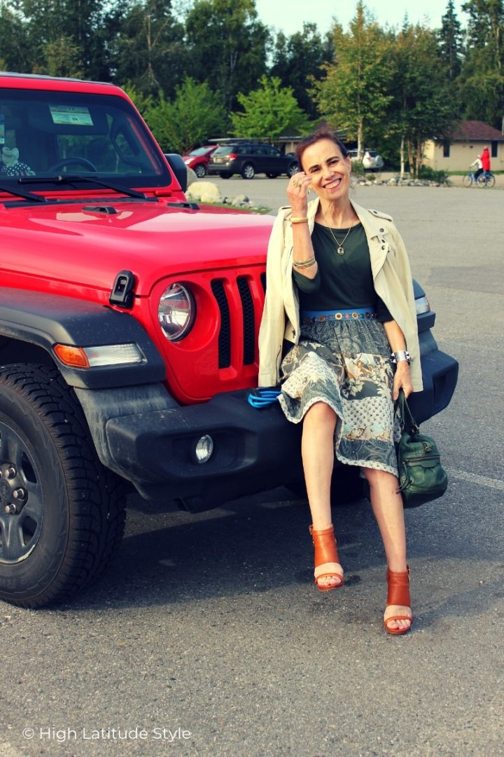 Alaskan woman sitting on the bumper of a jeep Wrangler in heels, tiered skirt, top, heels and motorcycle leather jacket