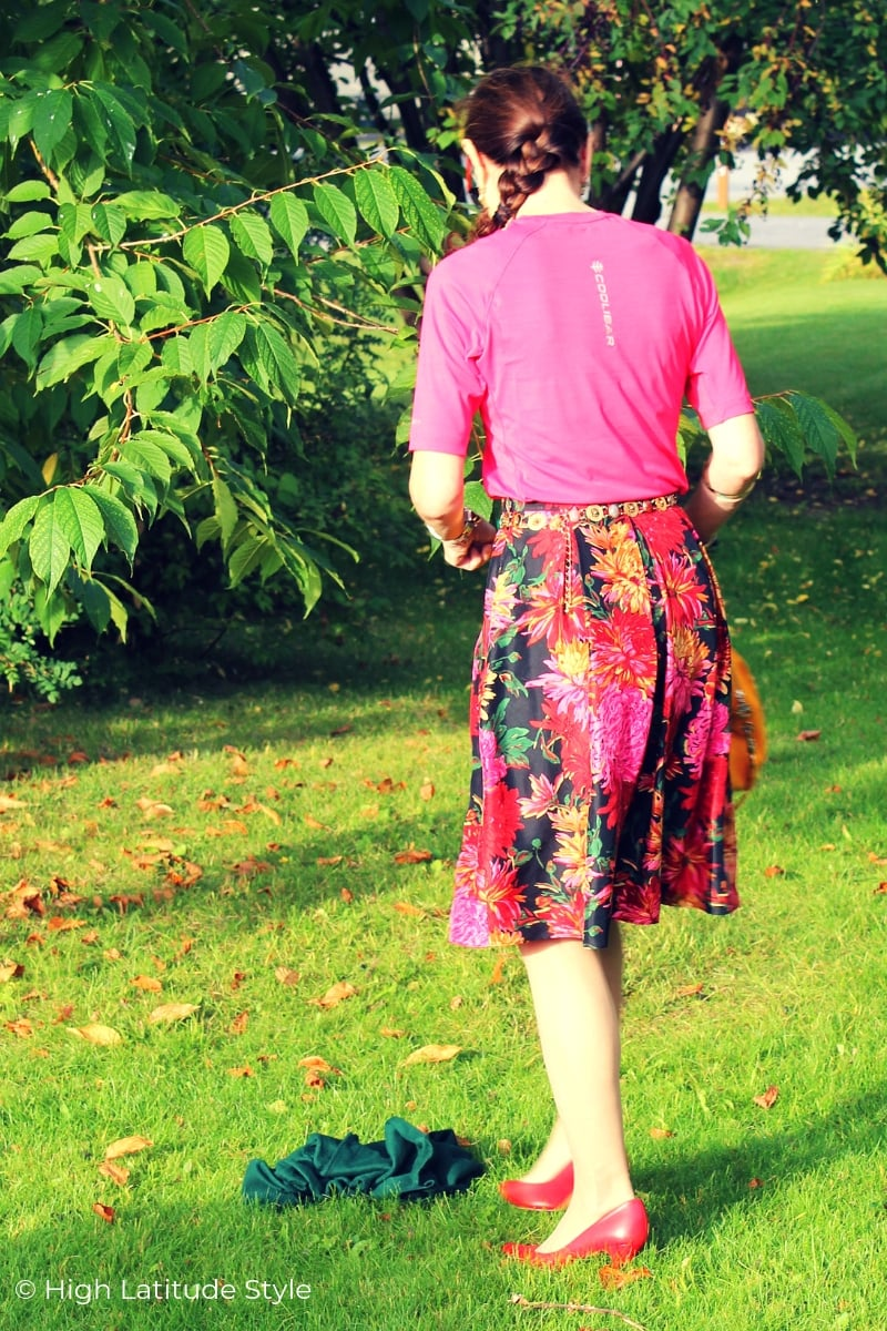 mature woman on a lawn in pink top floral skirt in fall