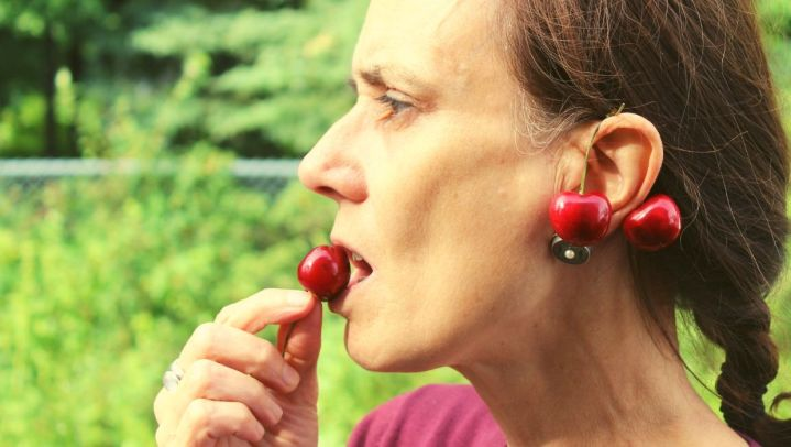 older woman with cherries hanging on her ear eating a cherry