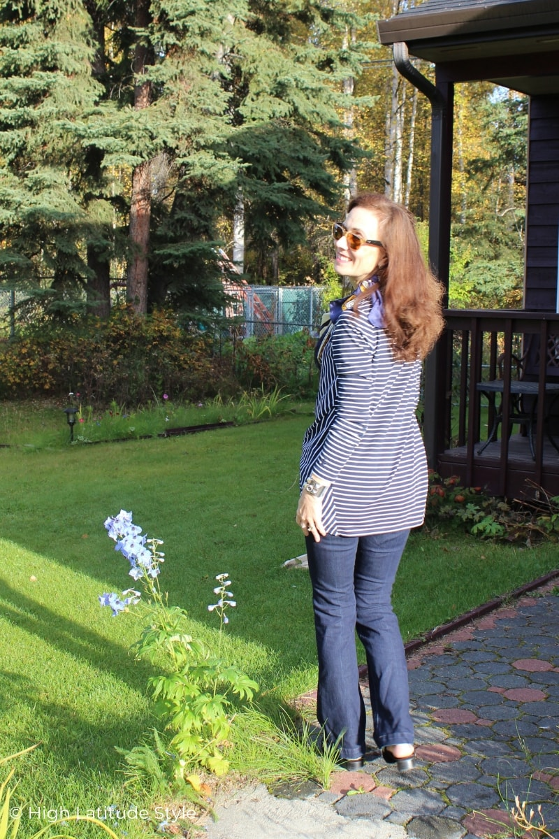 Alaskan woman standing in Coolibar top and jeans in a garden in September
