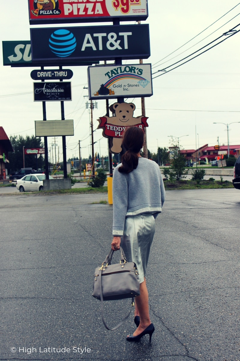 mature woman walking in a paved parking lot in gray silver outfit