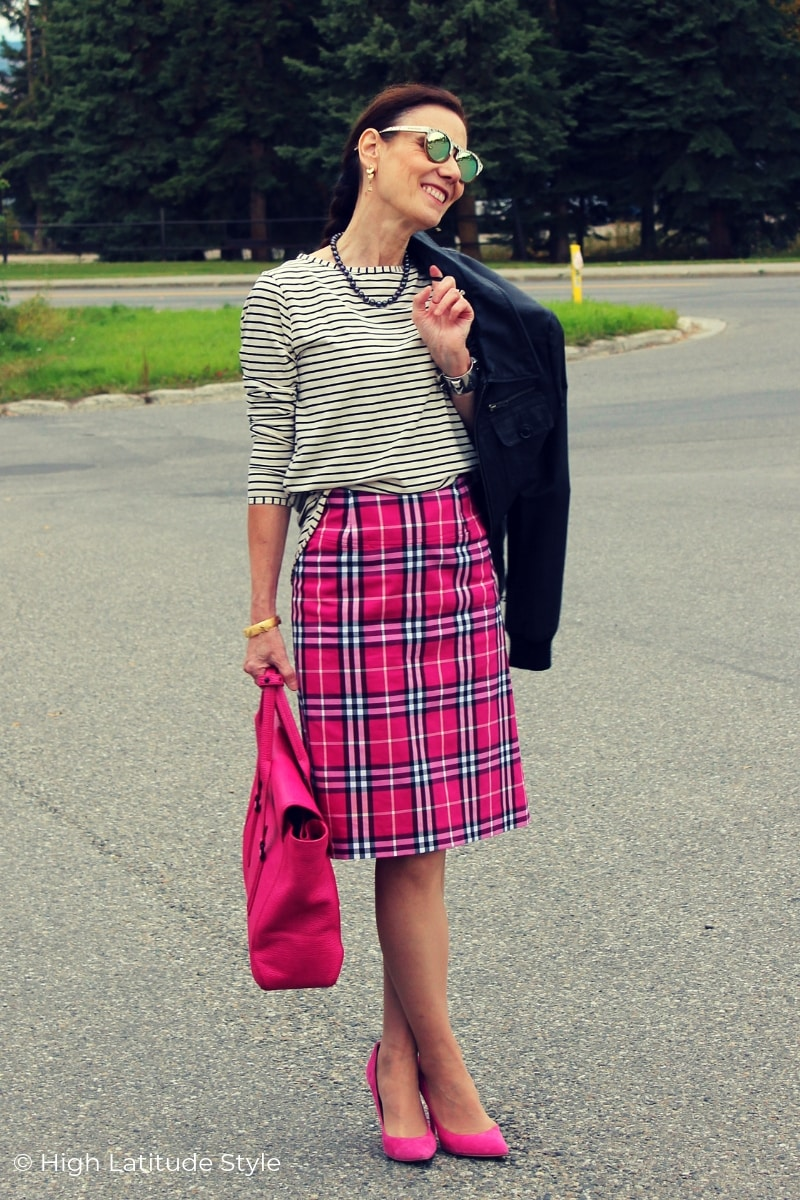 style book author wearing tartan, stripes leather and pink in one business casual outfit