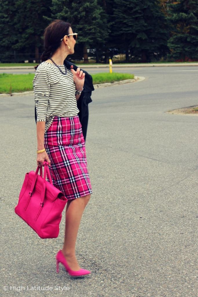 midlife blogger in tartan knee length skirt, striped Tee, pink pumps and bag