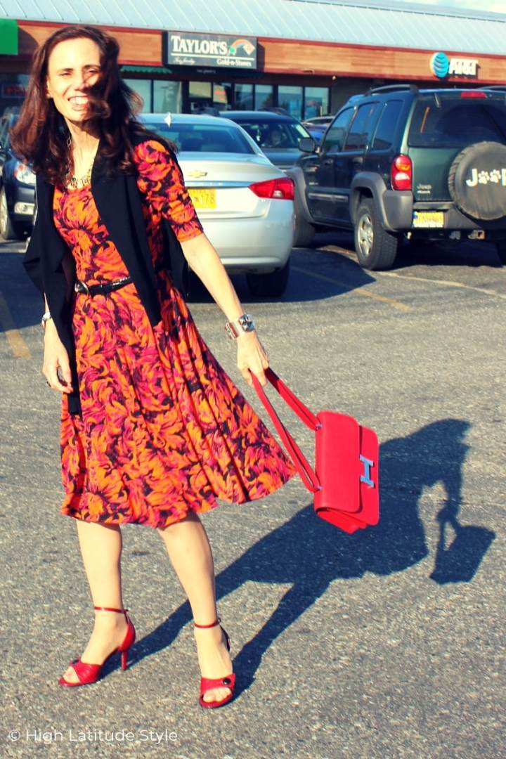 Nicole of High Latitude Style in abstract print dress with belt and jacket playing with the shadow