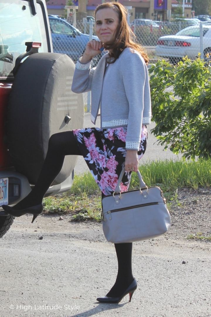mature style blogger donning black hosiery with a black, pink, gray dress and gray jacket